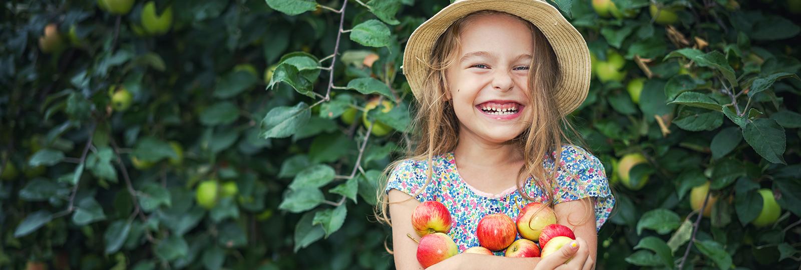 Lachendes Mädchen mit Äpfeln im Arm