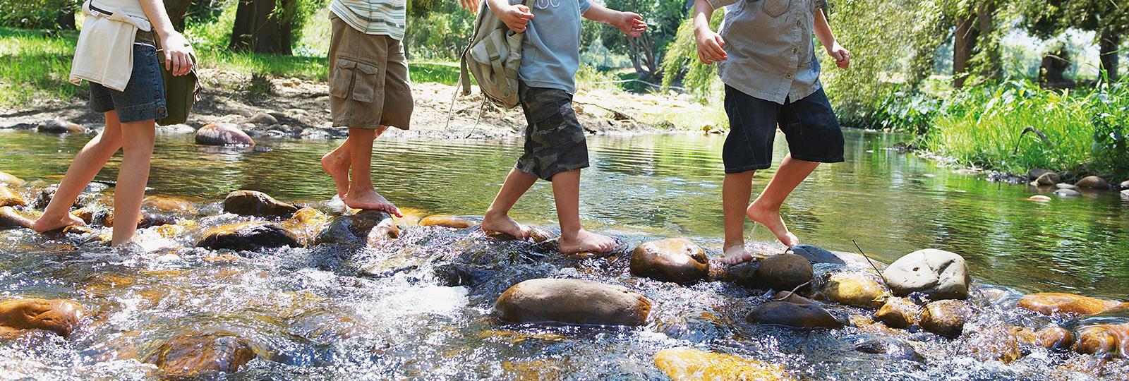 Kinder gehen auf Kieselsteinen durch einen Bach