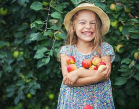 Lachendes Mädchen mit Äpfeln im Arm, Foto: Fotolia